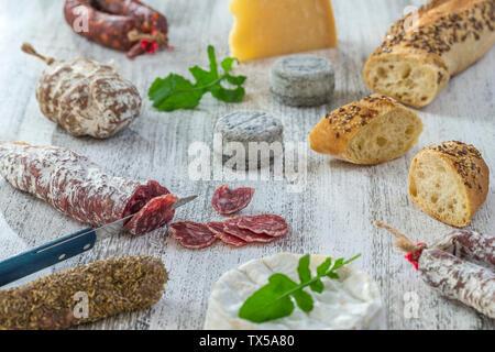 Des collations avec du vin français - divers types de fromages, pain , les saucissons secs, charcuterie, vigne rouge sur un fond gris. Vue d'en haut. Arrière-plan de l'alimentation