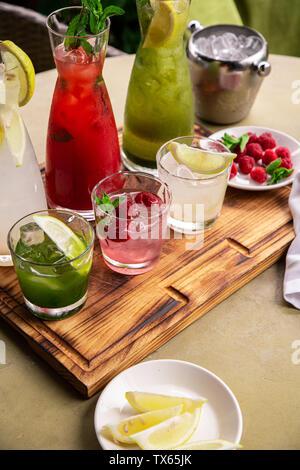 Les boissons d'été, un ensemble de limonades. Les limonades dans pichets sur la table, les ingrédients qui les composent sont disposés autour.