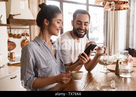 Photo d'brunette couple homme et femme 20s à boire du café et à l'aide de téléphone cellulaire durant le petit-déjeuner dans la cuisine à la maison Banque D'Images