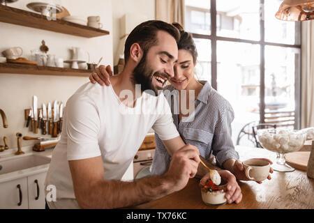 Photo de jolie brunette couple homme et femme 20s de boire du café et manger des desserts au petit-déjeuner dans la cuisine à la maison Banque D'Images