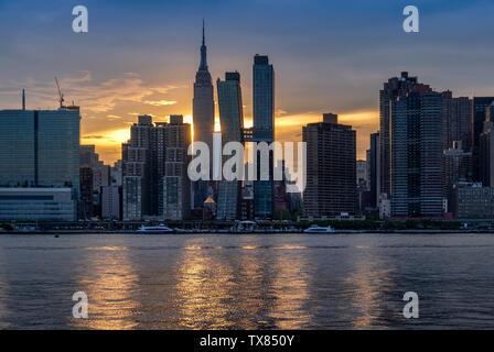 L'horizon de Manhattan et l'Empire State Building à travers l'East River au coucher du soleil, Manhattan, New York, USA