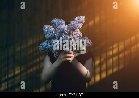 Girl holding bouquet de lilas en face du visage. Bénéficiant de l'enfant à l'extérieur de fleurs en face du mur. Kid se cacher derrière bouquet de fleurs violettes. L'été et printemps flore. Jeune personne avec don en mains