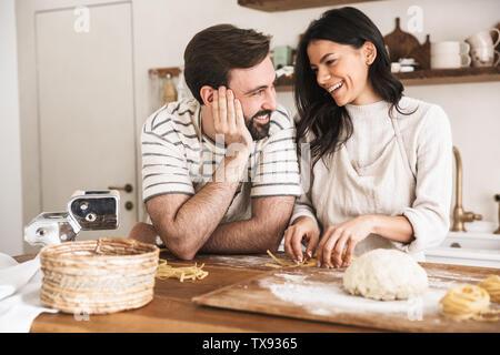 Portrait de l'homme et la femme couple positif 30s portant des tabliers des pâtes de la pâte pendant la cuisson ensemble dans la cuisine à la maison Banque D'Images