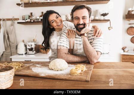 Image de l'homme et de la femme de la famille positive 30s portant des tabliers des pâtes de la pâte pendant la cuisson ensemble dans la cuisine à la maison Banque D'Images