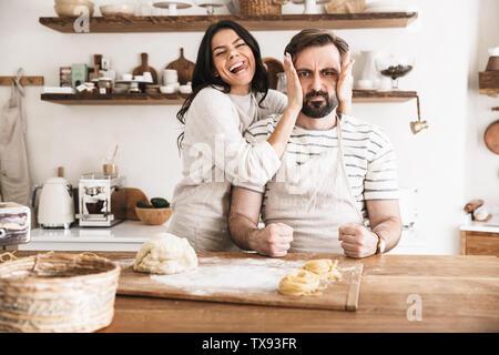 Image amusante de couple homme et femme 30s portant des tabliers de s'amuser ensemble tout en faisant des pâtes dans la cuisine à la maison Banque D'Images