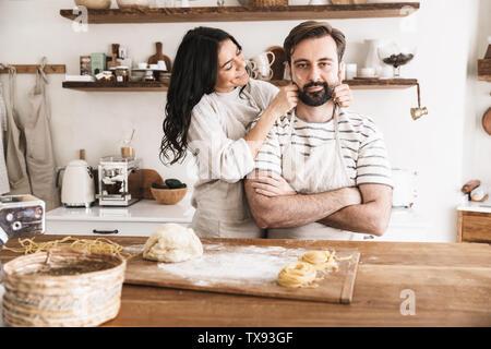Image de l'heureux couple homme et femme 30s portant des tabliers de s'amuser ensemble tout en faisant des pâtes dans la cuisine à la maison Banque D'Images