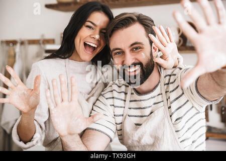 Image de l'homme et la femme couple positif 30s portant des tabliers s'amuser tout en faisant des pâtes dans la cuisine à la maison Banque D'Images