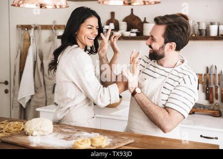 Image couple homme et femme 30s portant des tabliers s'amuser tout en faisant des pâtes dans la cuisine à la maison Banque D'Images