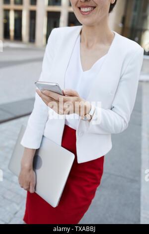 Mid section portrait of smiling businesswoman holding smartphone tout en se posant à l'extérieur dans la zone d'affaires, copy space Banque D'Images