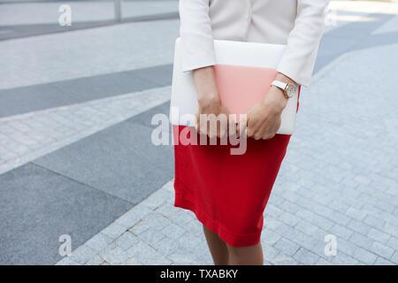 Le milieu de l'article portrait d'élégante jeune femme portant jupe rouge et holding laptop, copy space Banque D'Images