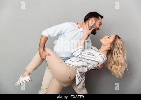 Photo gros plan du couple amoureux en habits de sourire et de danser au mur gris isolé Banque D'Images