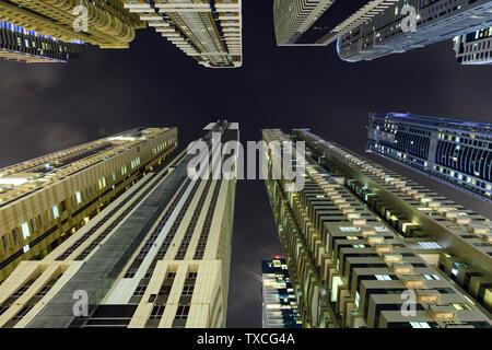 (Point de vue différent) Superbe vue du bas vers le haut de certains des gratte-ciel et tours allumés pendant la nuit à la Marina de Dubaï.