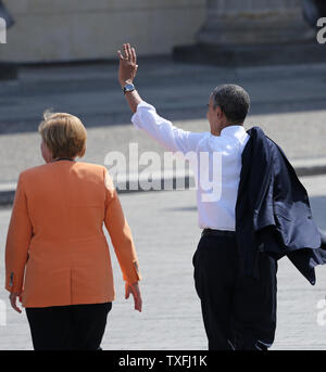 """Le président américain Barack Obama (R) et la Chancelière allemande, Angela Merkel, laisser la porte de Brandebourg après avoir donné un discours à l'emplacement historique à Berlin le 19 juin 2013. Obama est à Berlin pour sa première visite officielle à l'Allemagne et a parlé à l'endroit même où cinquante ans plus tôt, le président américain John F. Kennedy a prononcé son célèbre """"Ich bin ein Berliner (je suis un Berliner)' adresse . UPI/David Silpa Banque D'Images"""