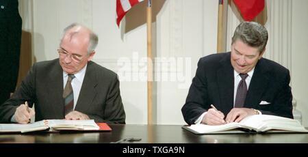 Secrétaire général Mikhail Gorbatchev (à gauche) et du président américain Ronald Reagan (à droite) signe les forces nucléaires à portée intermédiaire (FNI). Washington, Maison Blanche, 8 décembre 1987 Banque D'Images