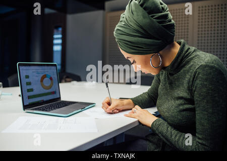 Businesswoman writing notes et using laptop in office