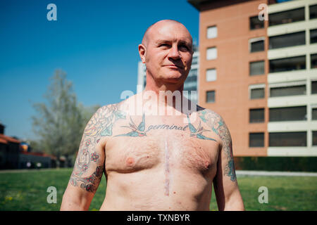 La gymnastique en parc, torse nu tatoué mature man, portrait Banque D'Images