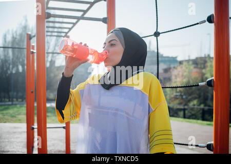 La classe de gymnastique suédoise au sport en plein air, jeune femme à boire de l'eau bouteille