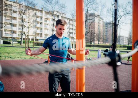La gymnastique au sport en plein air, jeune homme d'armes qui s'étend sur l'équipement d'exercice