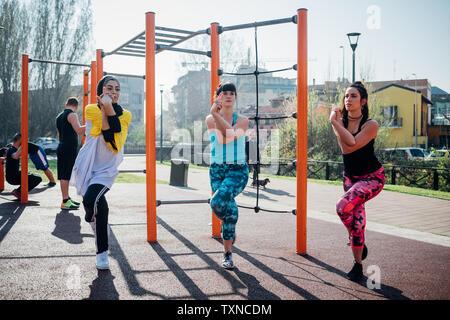 La classe de gymnastique suédoise au sport en plein air, les jeunes femmes en équilibre sur une jambe