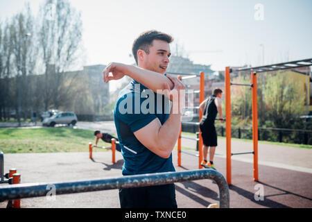 La gymnastique au sport en plein air, jeune homme bras étirement