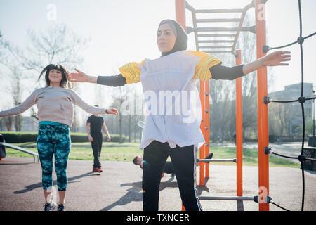 La classe de gymnastique suédoise au sport en plein air, les jeunes femmes jumping with arms outstretched