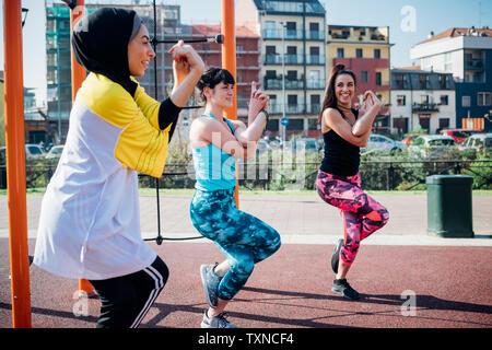 La classe de gymnastique suédoise au sport en plein air, les jeunes femmes en équilibre sur une jambe, side view