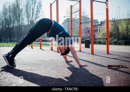 La gymnastique au sport en plein air, jeune homme en bas yoga pose