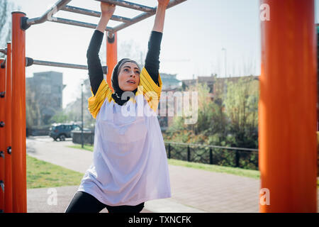 La classe de gymnastique suédoise au sport en plein air, jeune femme accrochée à l'équipement d'exercice