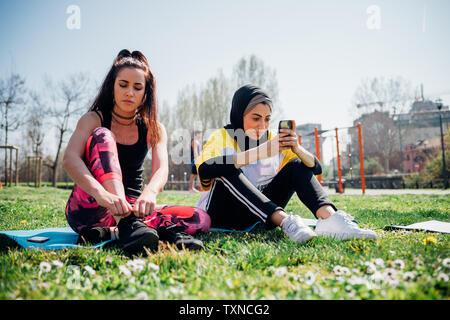 La classe de gymnastique suédoise au sport en plein air, les jeunes femmes sitting on grass lacets de liage et looking at smartphone