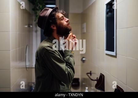 Jeune homme barbu barbe brossage dans la salle de bains Banque D'Images