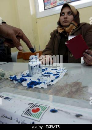 Un membre des forces de sécurité palestiniennes que les encres son doigt qu'il vote pour l'assemblée législative palestinienne candidats à une élection station sur le deuxième jour du scrutin, le 22 janvier 2006 dans la ville de Gaza, la bande de Gaza. Officiers et soldats de la sécurité palestinienne a voté pour la deuxième journée consécutive à un début de scrutin pour l'élection présidentielle afin qu'ils soient libres d'assurer la sécurité. (Photo d'UPI/Ismael Mohamad) Banque D'Images