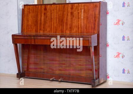 Touches de piano en bois sur l'instrument de musique en bois en vue de face . Piano en bois ancien. Piano brun installée contre le mur .