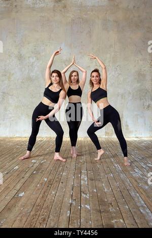 Trois belles filles de remise en forme, souriant posant dans une salle de remise en forme. Sport Concept, le travail d'équipe. Fond gris Banque D'Images