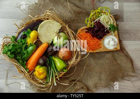 Légumes frais, oignons, choux, betteraves, carottes, poivrons,dans un panier en osier et des légumes râpés sur un plateau en bois en forme de cœur avec s Banque D'Images