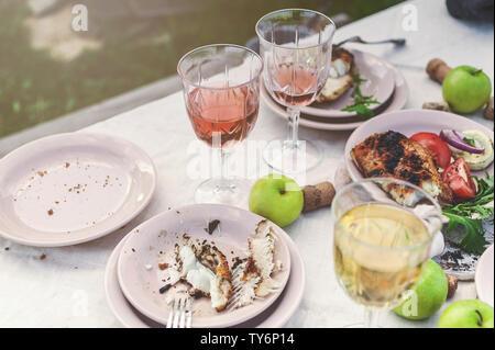 Verres de vin blanc et rose, du poisson grillé, des plaques, légumes, salades et fruits sur la table. Fête de l'été dans l'arrière-cour. Plan horizontal Banque D'Images
