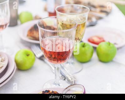 Le mérou grillé, des verres avec du vin blanc et rose, des assiettes, des légumes, de la salade et des fruits sur la table. Fête de l'été dans l'arrière-cour. Plan horizontal Banque D'Images
