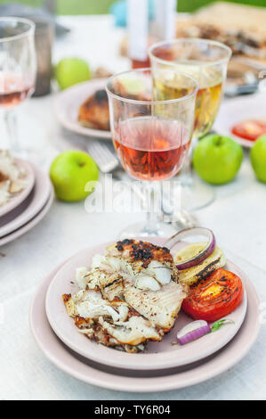 Le mérou grillé, des verres avec du vin blanc et rose, des assiettes, des légumes, de la salade et des fruits sur la table. Fête de l'été dans l'arrière-cour. Shot verticale