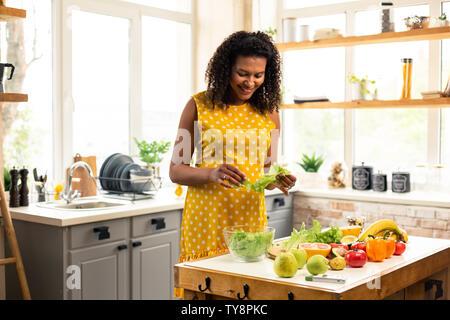 Pregnant woman making salad dans sa cuisine. Banque D'Images