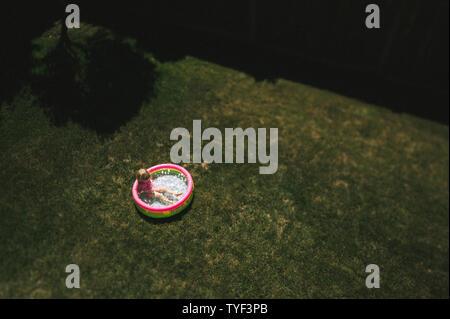 Une jeune fille joue dans une petite cour extérieure sur la pelouse. Banque D'Images