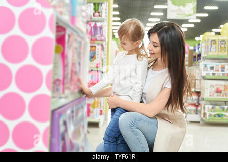 Vue latérale du séduisant jeune mère choisissant poupée avec ma petite fille en boutique. Cheerful woman standing près de jouets, parler et sourire en supermarché. Concept de shopping et de la famille.