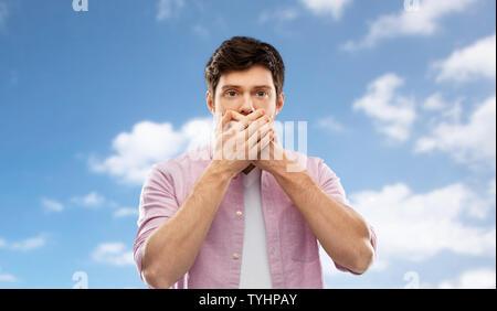 Choqué par la main de l'homme couvrant la bouche plus de ciel bleu Banque D'Images