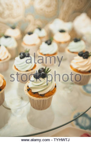 Cupcakes à la vanille avec glaçage à la crème, décoré avec des bleuets, des gros plan sur un plat en verre sur la table de mariage. Le concept de l'alimentation, de sucreries. Banque D'Images