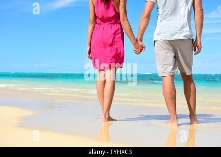 Beach couple amoureux se tenant la main en lune de miel. La partie inférieure du corps montrant récolte robe rose, occasionnels de plage, les jambes et les pieds des jeunes mariés romantiques personnes debout sur le sable blanc sur les vacances d'été. Banque D'Images