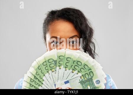 African American Woman se cachant derrière l'argent Banque D'Images