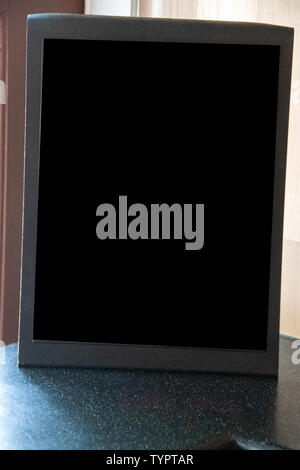Petite black blank chalkboard signer sur une table Banque D'Images