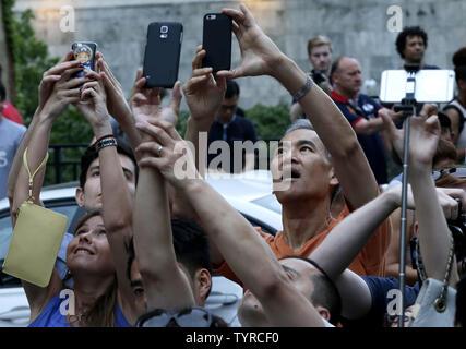 Les gens se rassemblent et prendre des photos en vue de la 42e rue à Manhattan dans l'espoir de voir un événement Manhattanhenge qui n'auraient jamais apparaître en raison de nuages lourds dans la ville de New York le 29 mai 2016. Le Manhattanhenge coucher du soleil vient deux fois par an lorsque le soleil qui soit parfaitement aligné avec le Manhattan street grille. Photo de John Angelillo/UPI Banque D'Images