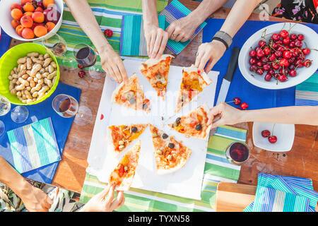 Des mains amies partager tranches de pizza à partir d'une table chargée de fruit au cours d'une fête d'été. Banque D'Images