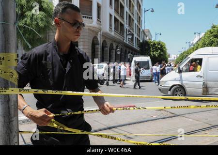 Tunis, Tunisie. 27 Juin, 2019. Un homme de la police s'étend une barricade tape pour boucler la scène où une personne s'est fait exploser près d'une voiture de police blessant cinq personnes, à l'Avenue Charles de Gaulle. Credit: Khaled Nasraoui/dpa/Alamy Live News Banque D'Images
