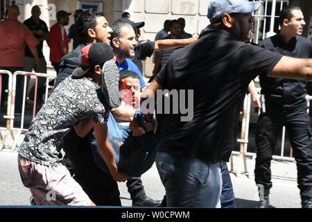 Tunis, Tunisie. 27 Juin, 2019. Les gens portent un policier blessé à l'ambulance de l'emplacement d'une bombe à Tunis, Tunisie, le 27 juin 2019. Deux membres de forces de sécurité tunisiennes ont été blessés jeudi dans un attentat suicide sur un véhicule de police stationné sur la Rue Habib Bourguiba dans le centre de Tunis, a indiqué Xinhua. Credit: Adele Ezzine/Xinhua/Alamy Live News Banque D'Images
