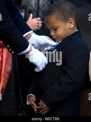 Un officier aide Rosa Parks grand neveu Schuyler McCauley Brown avec sa cravate avant le service funèbre pour parcs à la Metropolitan AME Le 31 octobre 2005 à Washington, DC. Plus de 30 000 personnes à la U.S. Capitol Rotunda adoptée par le cercueil de la femme qui a refusé de céder sa place à un homme blanc dans un bus de la ville de Montgomery en Alabama en 1955, l'origine de l'American Civil rights movement. (Photo d'UPI/Kamenko Pajic) Banque D'Images